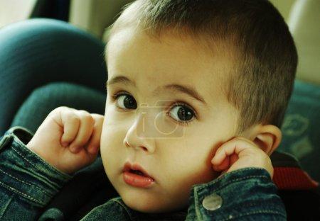 Photo pour Garçon s'arrête les oreilles avec les doigts, en évitant le bruit de la circulation dans la voiture - image libre de droit