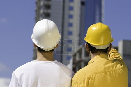 Photo for Under construction concept, two builders discuss building,focus point on heads - Royalty Free Image