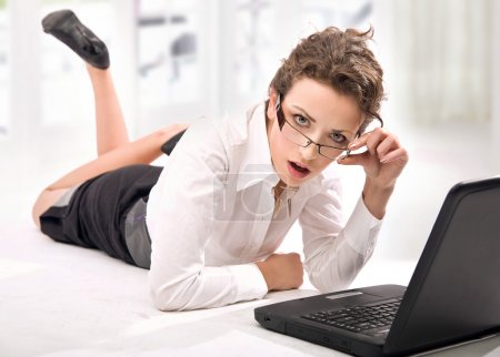 Happy young businesswoman with laptop on the floor
