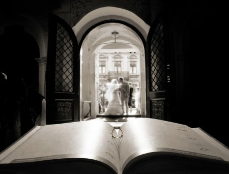 Book and ring over church door background