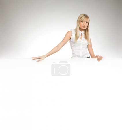 Attractive blonde over white empty board, lots of copyspace