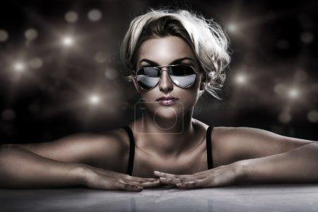 Studio shot of young blonde wearing stylish sunglasses