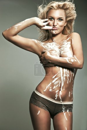 Young blond woman doused with paint