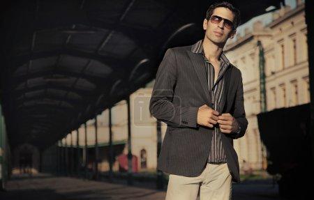 An elegant man next to a train