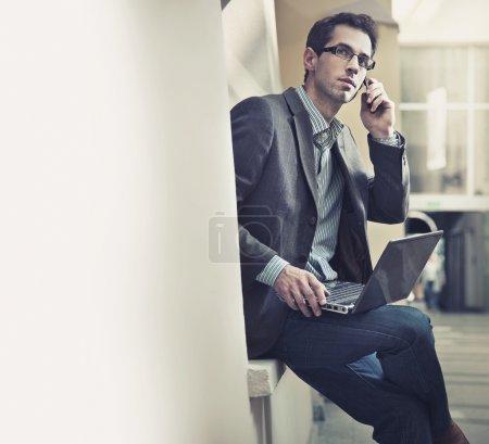 Photo pour Jeune homme d'affaires parlant par téléphone portable - image libre de droit