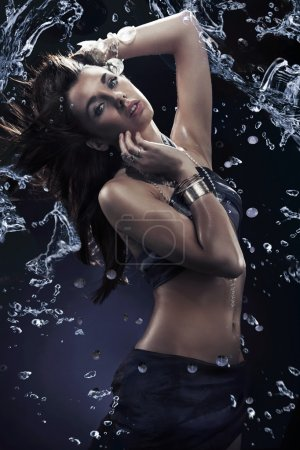 Young beauty dancing with water splash