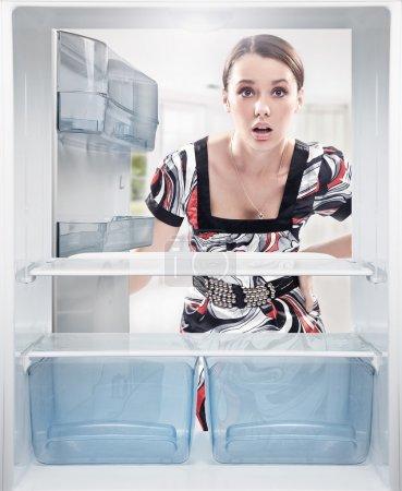 Photo pour Jeune femme à la recherche sur une étagère vide frigo. - image libre de droit