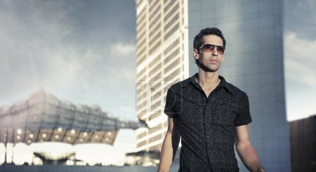 Young handsome man over urban background