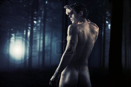 Fine art photo of a young muscular man in a forest