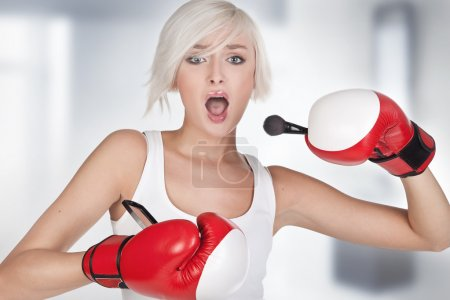 Young beauty doing make up in boxing gloves