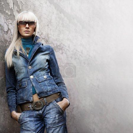 Photo pour Portrait d'une fille casual chic avec lunettes de soleil devant un mur - image libre de droit