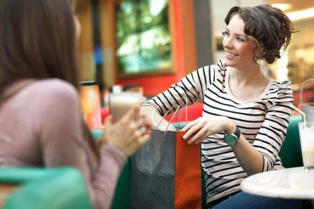 Photo pour Superbes femmes après avoir fait du shopping parler avec un ami - image libre de droit