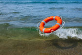 Red lifebuoy flying in the sea wave