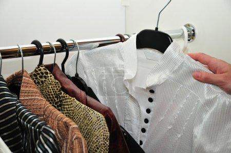 Photo pour Choix d'un chemisier blanc dans une armoire - image libre de droit