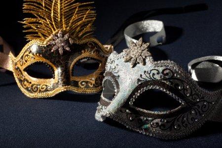 Photo pour Masques de carnaval argent et noir isolés sur un fond noir - image libre de droit