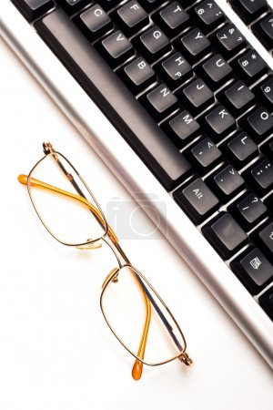 Photo for Fragment of keyboard with glasses, white background - Royalty Free Image