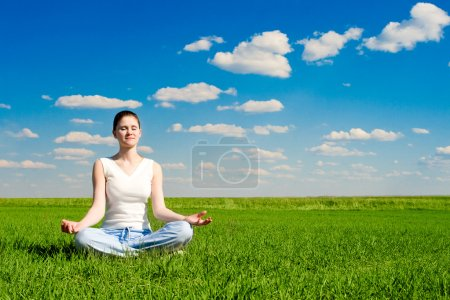 Photo for Meditation on the meadow over the blue sky - Royalty Free Image