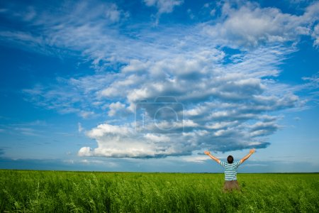 Photo for Man in summer field under clouds on blue skies - Royalty Free Image