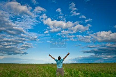 Photo pour Homme dans un champ vert sous un ciel bleu - image libre de droit