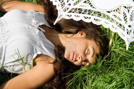 Pretty girl in white sleeping on the grass