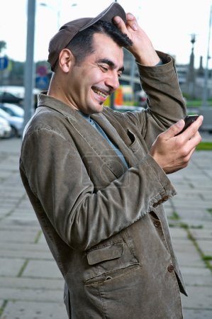Happy man with mobile phone outdoors