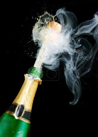 Photo pour Bouchon de champagne volant ; objets sur fond noir - image libre de droit