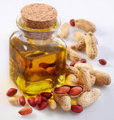 Peanut oil with nuts on a white background