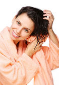 Smiling young woman drying hair with towel in a bathrobe on a white backgr