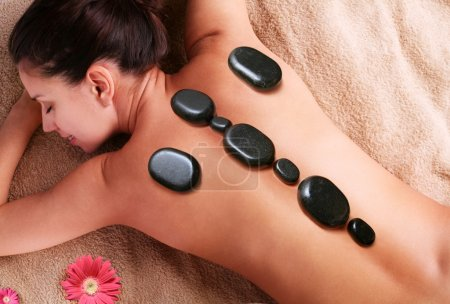 Smiling young woman getting pleasure of stone therapy. Eyes are closed.