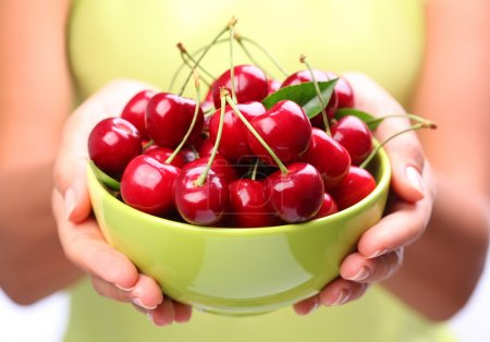 Crockery with cherries in woman hands.