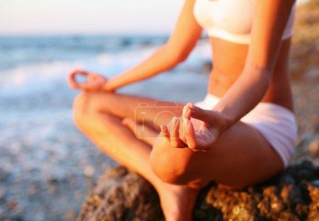 Photo pour Corps d'une belle jeune fille dans une méditation sur la plage - image libre de droit