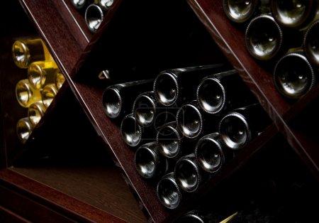 Photo pour Instantané de la cave à vin. les bouteilles sur les étagères en bois. - image libre de droit