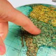 Image shows an old terrestrial globe with a finger...