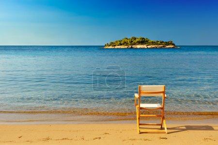 Photo pour Une chaise sur une plage de sable offrant un endroit pour profiter de la vue et de la sérénité de l'emplacement - image libre de droit
