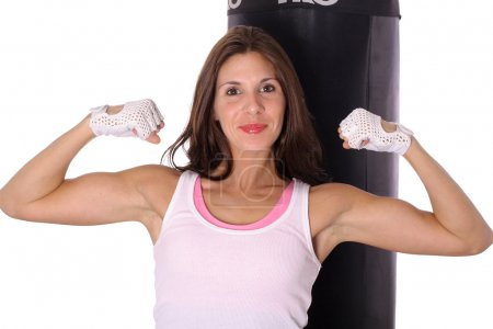 Fitness girl flexing in front of punching bag