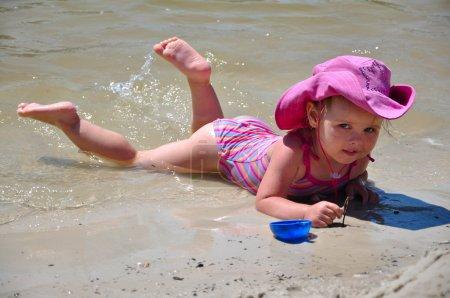 Foto de Niña bonita tumbado en la playa de arena junto al mar - Imagen libre de derechos