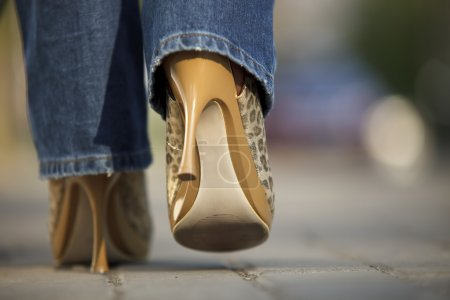 Close-up of female in jaguar spotted shoes walking