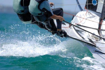 Photo pour Bateau à voile dynamitage à travers des vagues pendant la course. - image libre de droit