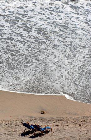 Photo pour Chaises de plage sur le sable par l'océan - image libre de droit