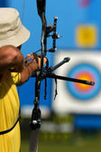 male archer takes aim at target