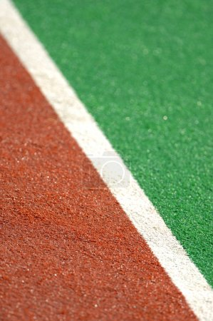 Track and field with green artificial turf on fiel...
