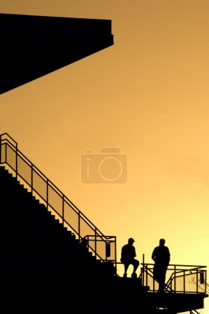 silhouettes at sunset stadium stairs