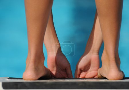 Photo for Female swimmer on starting block, cropped, rear view - Royalty Free Image