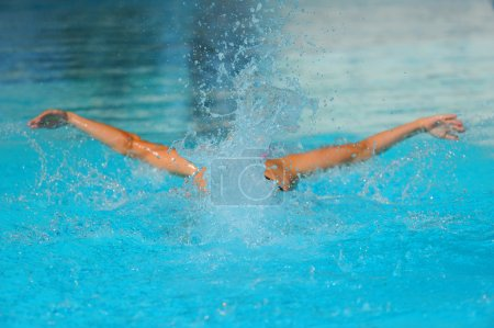 Swimmer powering through the water of a pool