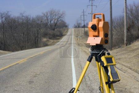 Photo pour Théodolite situé sur le bord de la route - arpentage printanier . - image libre de droit