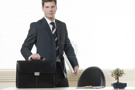 Photo pour Homme d'affaires dans son bureau avec mallette - image libre de droit