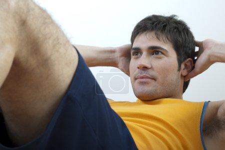 Young man doing sit-ups...