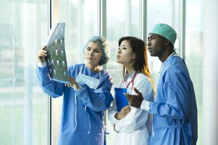 Photo pour Médecins multiethniques, discuter sur un examen de patients aux rayons x - image libre de droit