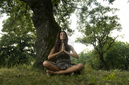 Beautiful young woman meditating in nature with hands joined.
