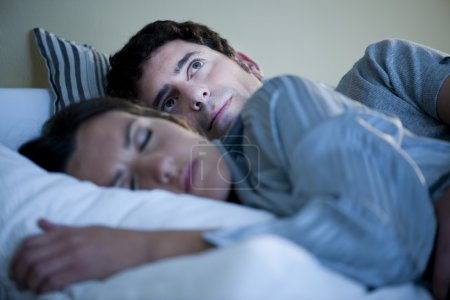 Photo for Image of a couple in bed, man cannot sleep - Royalty Free Image